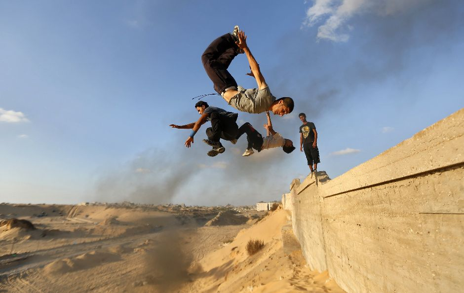 Palestinian youths practice their parkour skills in Khan Younis in the southern Gaza Strip