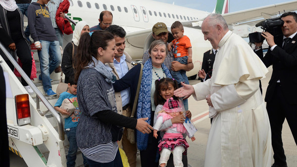 FILIPPO MONTEFORTE/EPA/MAXPPP - epa05262090 Pope Francis (R) welcomes a group of Syrian refugees that flew with him after landing at Ciampino airport in Rome, Italy, 16 April 2016. Pope Francis is taking twelve Syrian migrants with him to the Vativan after a visit to the Greek island of Lesbos on 16 April, in a trip aimed at supporting refugees and drawing attention to the frontline of Europe's migration crisis. EPA/FILIPPO MONTEFORTE